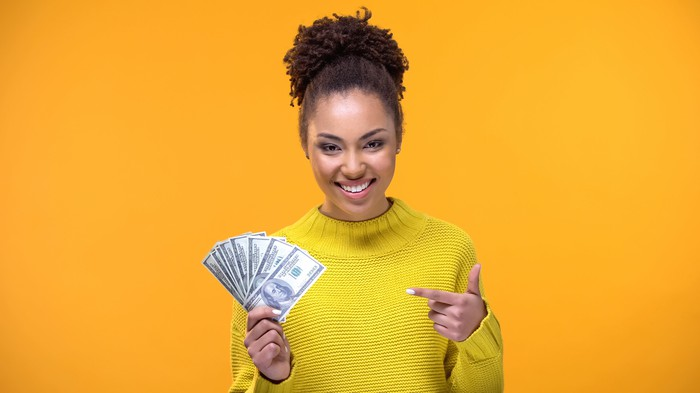 Smiling woman holding a bunch of hundred-dollar bills