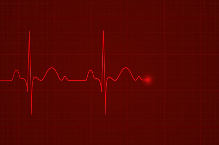 Glowing red heartbeat monitor graph flatlines