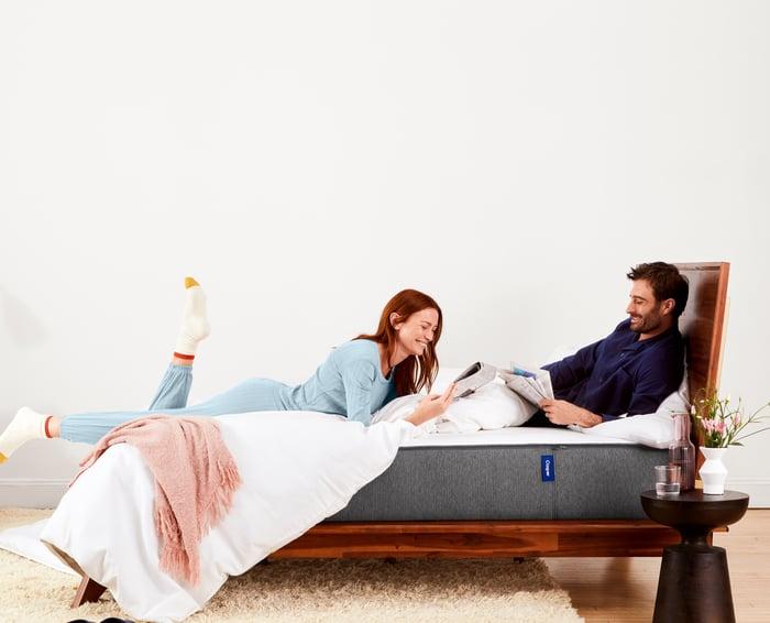A man and woman relaxing on a Casper mattress.