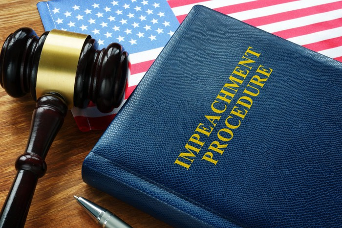 An impeachment procedure law book with a gavel and an american flag on a table.
