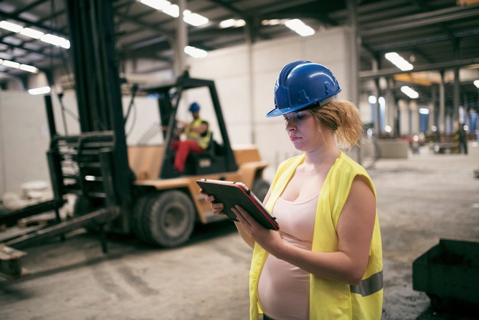 A pregnant woman in a hard hat holds a notebook computer on a construction site, with a forklift and its operator in the background.
