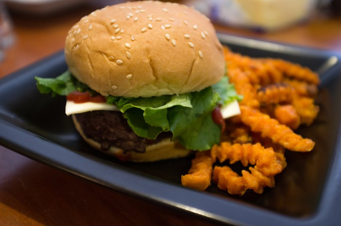 A cheeseburger with lettuce and crinkle fries.