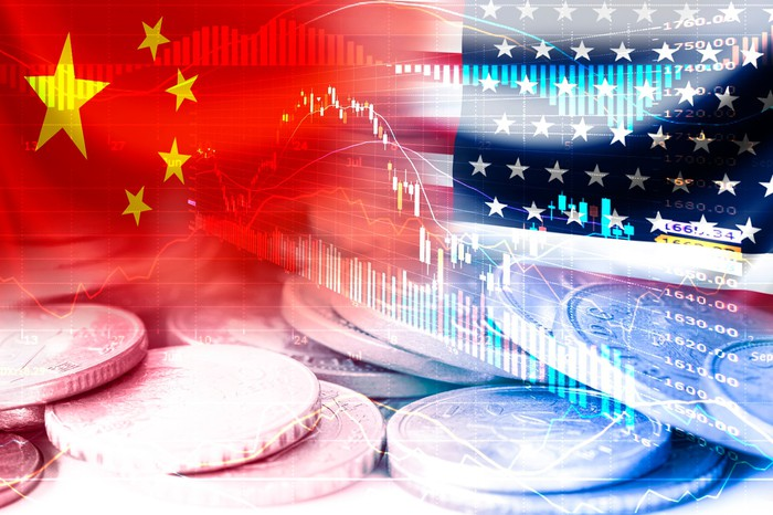 China and U.S. flags superimposed over coins and stock charts.