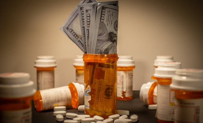 A bunch of $100 bills is stuffed into a prescription drug container, surrounded by other containers and pills spilled on a counter.
