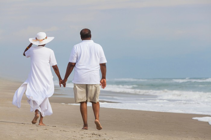 Older couple walking along a sandy beach.