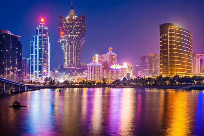 Skyline with several large buildings at night in front of a bay.