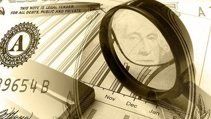 Magnifying glass on a dollar bill and some stock results