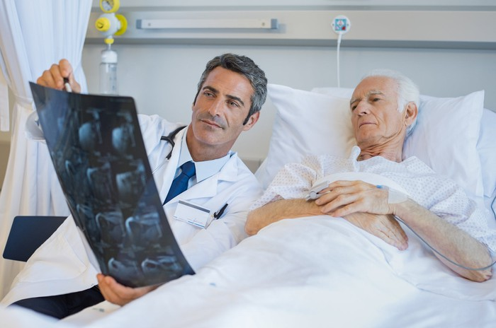 Doctor holding x-ray reading while older man lying in bed looks on