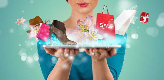 Items including a hat, a shoe, and a shopping bag with the word sale on it pop out of a tablet being held by a woman
