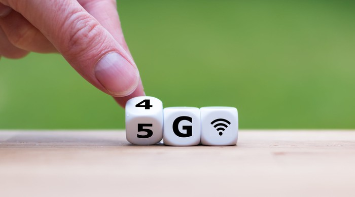 Three white dice spell out $G and a wireless signal symbol as a hand rolls the 4 over to spell 5G instead.