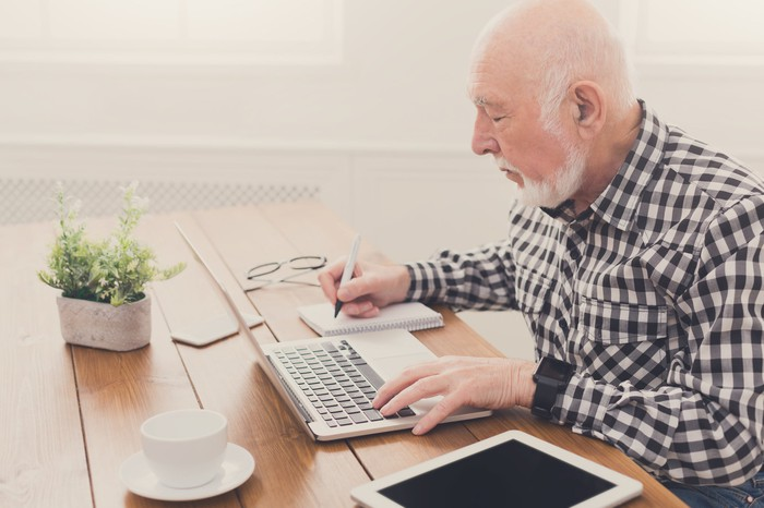 Older man typing on laptop while writing on a notebook