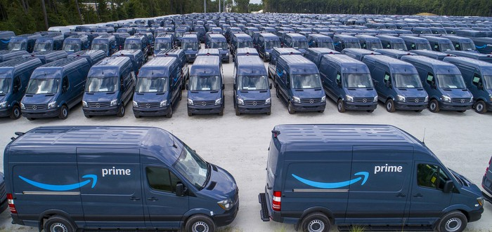 Several dozen dark blue Amazon Prime delivery trucks lined up in a large parking lot.