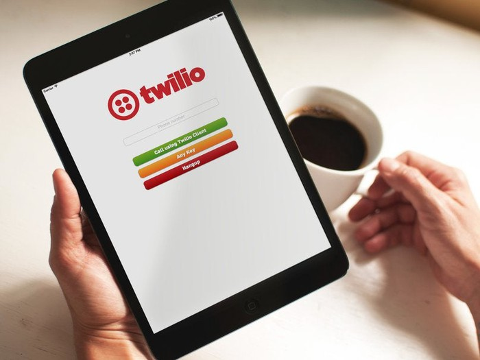 Twilio running on a tablet that's being held by someone holding a cup of coffee.