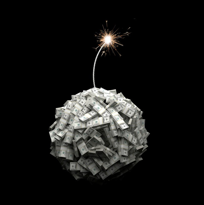 A bundle of dollar bills in the shape of a bomb with a lit fuse on top.