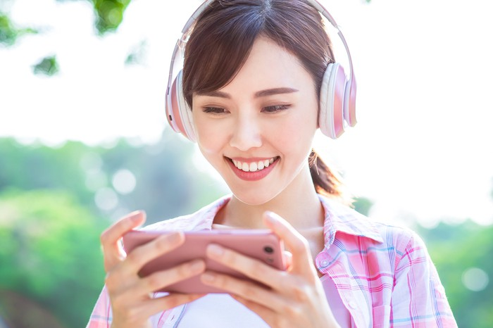 A young woman plays a smartphone game.