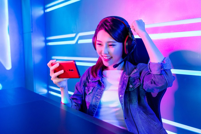 A young woman plays a mobile game on a smartphone.