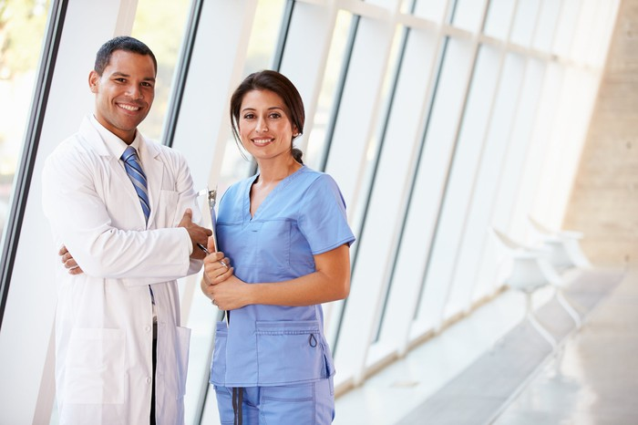 Male healthcare provider in white coat standing next to female healthcare provider in scrubs, both smiling.