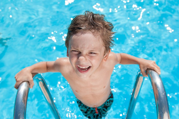 A boy with clear skin exiting a swimming pool.