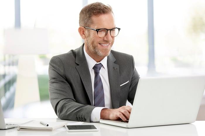 Smiling man in suit typing on laptop