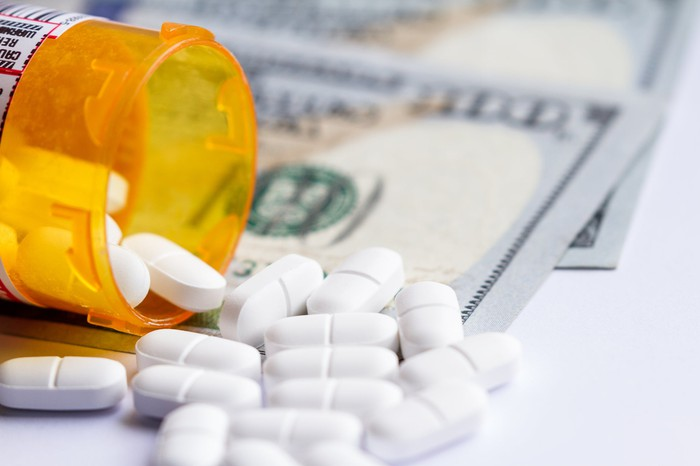 A tipped-over prescription container of white pills on top of cash.