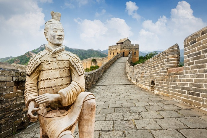 Statue of warrior on top of elevated brick walkway with walls and towers.