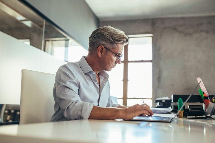 Man in collared shirt typing on laptop