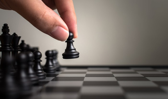 A hand moving a pawn on a chess board.