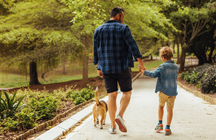 Man. boy, and dog walking outdoors