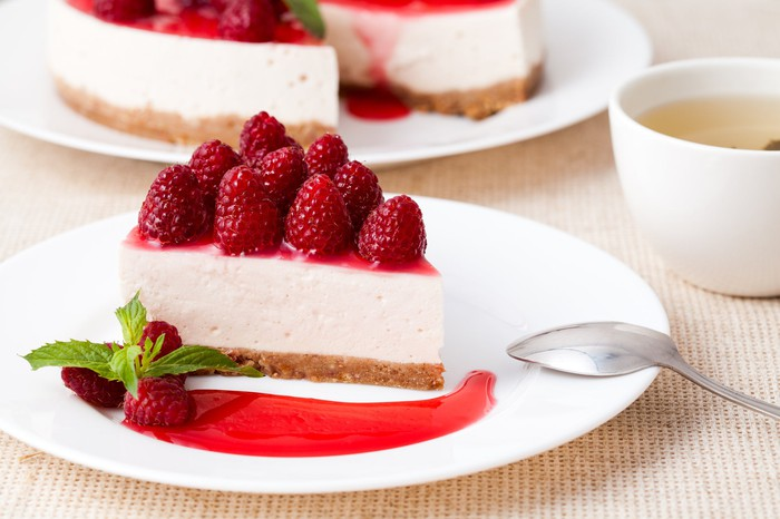 A slice of cheesecake topped with raspberries.