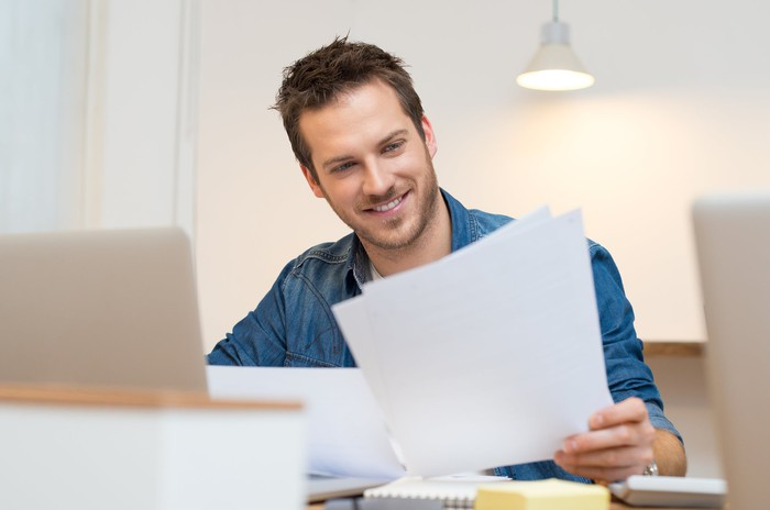 A man sitting at a desk in front of a laptop smiles as he reviews a document in his hand.