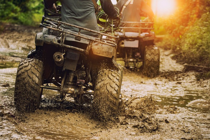 Riders on two offroad vehicles, seen from behind, make their way down a muddy trail toward the sun.