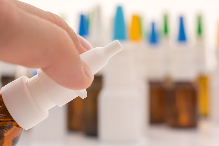 A person holding a nasal spray with several other sprays in the background.