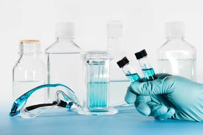 Hand holding two vials with blue liquid in front of lab glassware.