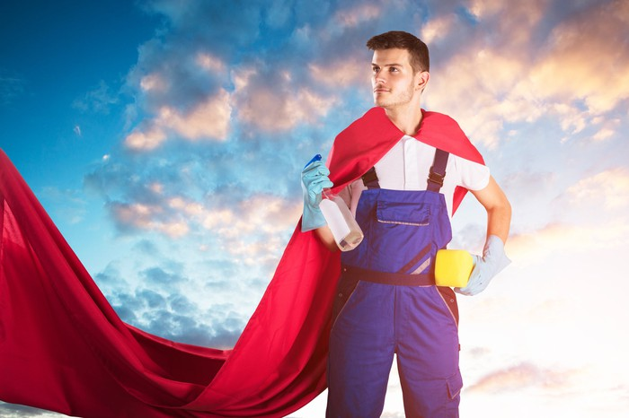 A man in blue overall worksuit is holding a bottle of cleaner and a sponge and has a red cape, looking like a superhero.