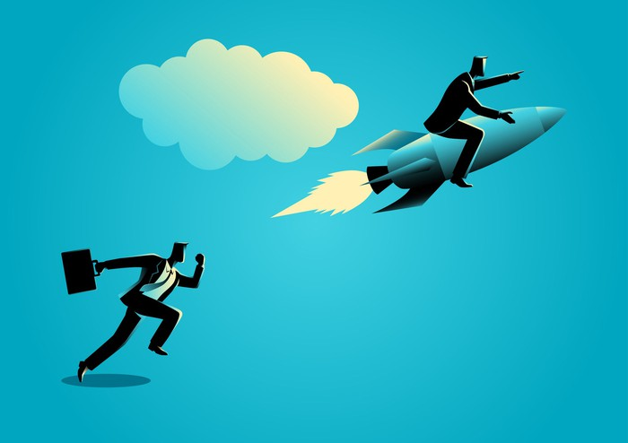 A businessman takes off on a rocket with another businessman running behind him.