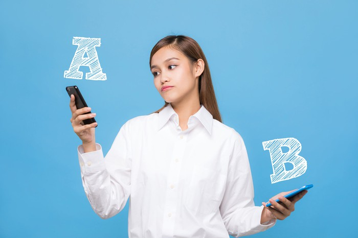A woman holds a smartphone in each hand. The letter A is above one; the letter B is above the other. She's looking at phone A.