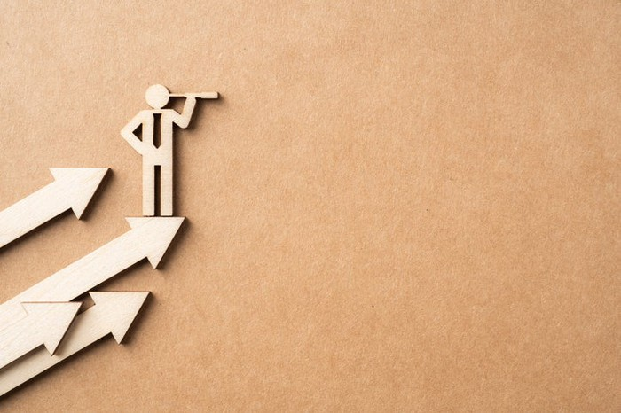 A paper cutout of a businessman stick figure standing on ascending arrows and looking through a monocle.