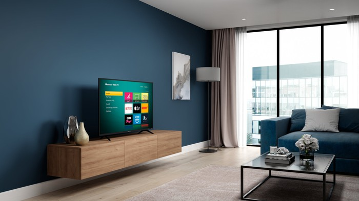 A TV displaying the Roku operating system in a living room.