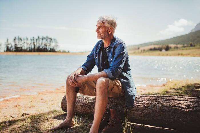 Older man sitting on tree log near lake.