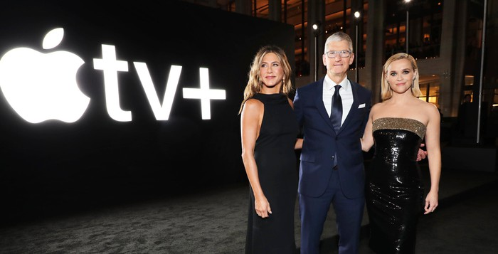 Tim Cook, Jennifer Aniston, and Reese Witherspoon standing in front of the Apple TV+ logo