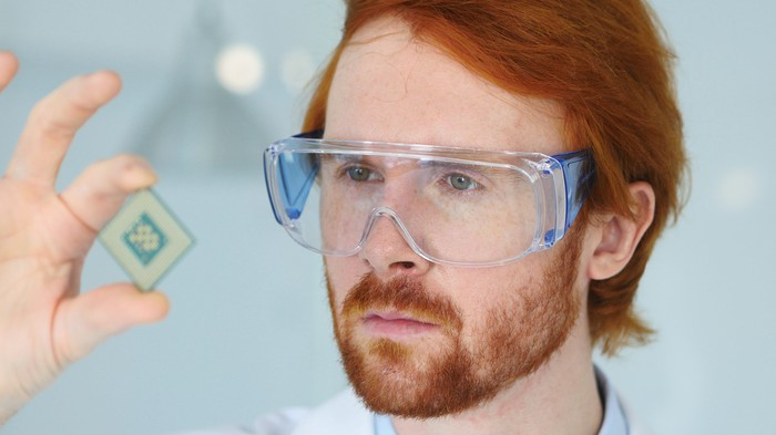 A technician with protective goggles looks closely at a computer chip.
