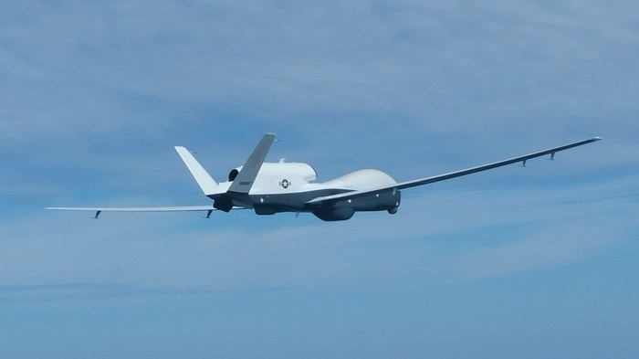 The Triton drone flies over blue skies.