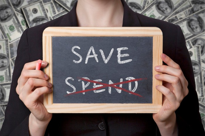 "Someone holding up a small blackboard, on which is printed the words ""save"" and ""spend,"" with the word ""spend"" crossed out."