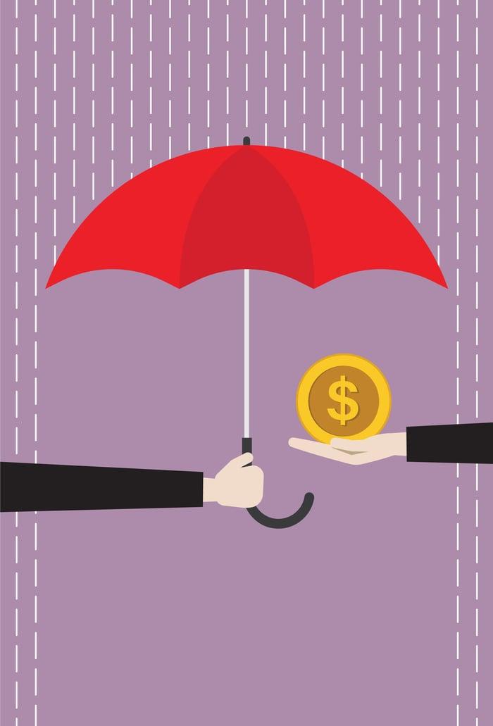 Money shielded from rain by umbrella.