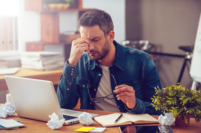 Man at laptop pinching his nose while holding eyeglasses, with several crumpled papers strewn about his desktop.