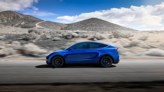 A blue Tesla Model Y on a desert road.