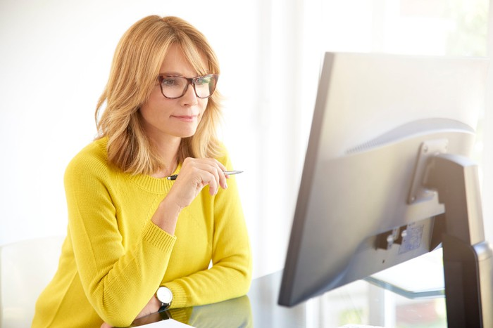 A middle-aged woman in yellow sweater looks at a large desktop monitor with a pen in her hand.