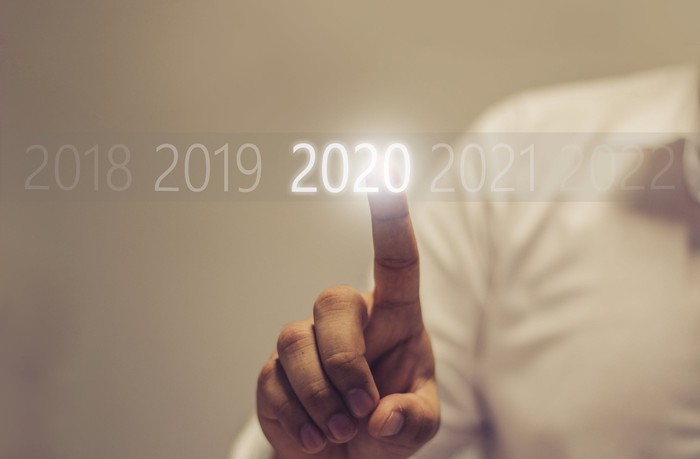 """A person touching a lit-up """"2020"""" display."""