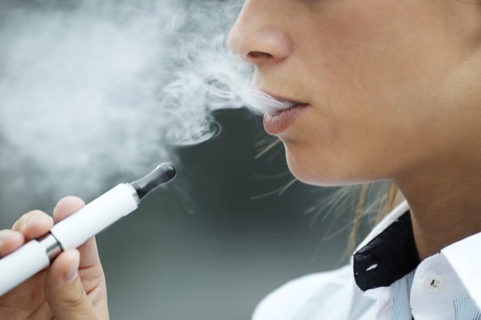 Woman smoking electronic cigarette.
