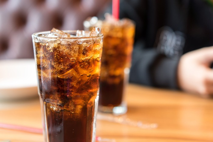 A glass filled with ice and dark cola with a similar glass out of focus in the background